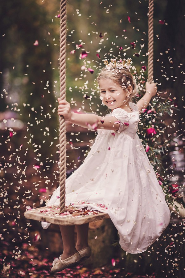 Flower girl on swing as confetti falls around her