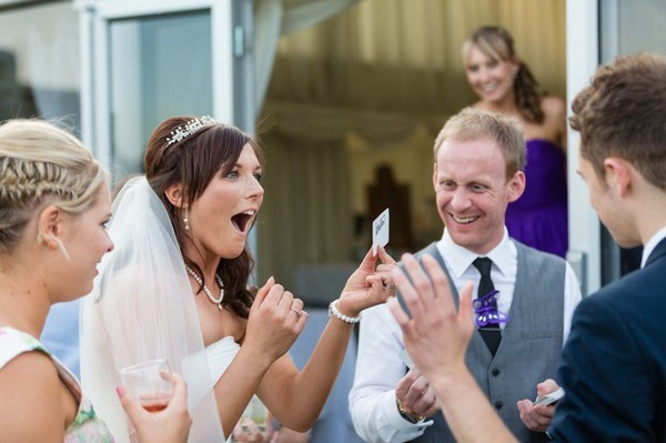 Bride taking part in magic trick with wedding magician