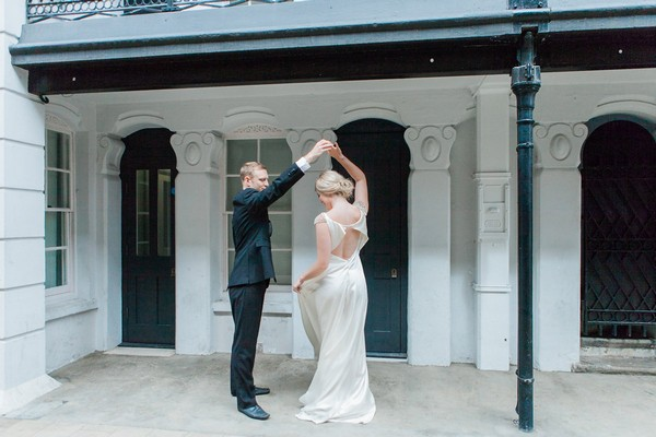 Groom holding bride's arm up as she twirls