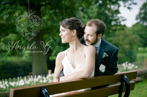 Bride and groom sitting on bench - Picture by Angela G Photographer
