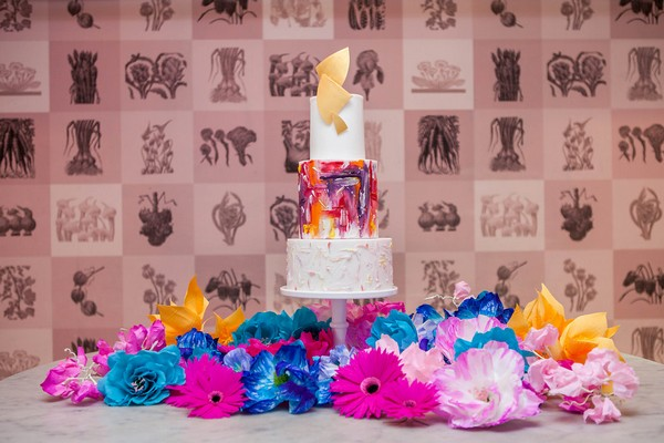 Colourful wedding cake surrounded by brightly coloured flowers