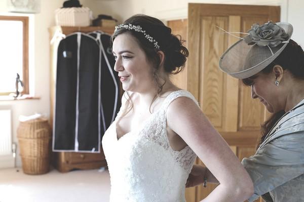 Bride having back of dress done up