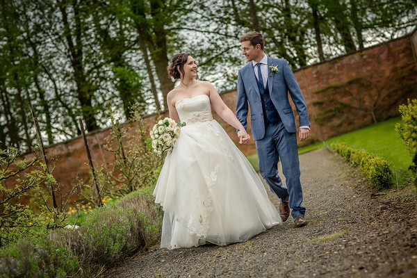 Bride and groom holding hands and walking in Sugnall Walled Garden