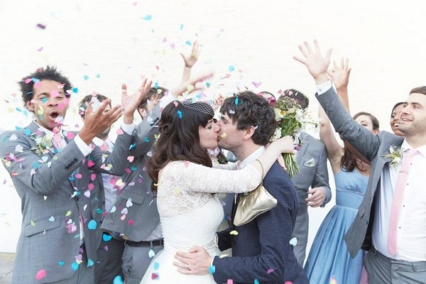 Bride and groom kissing as wedding guests throw confetti over them - Picture by Natalie J Weddings