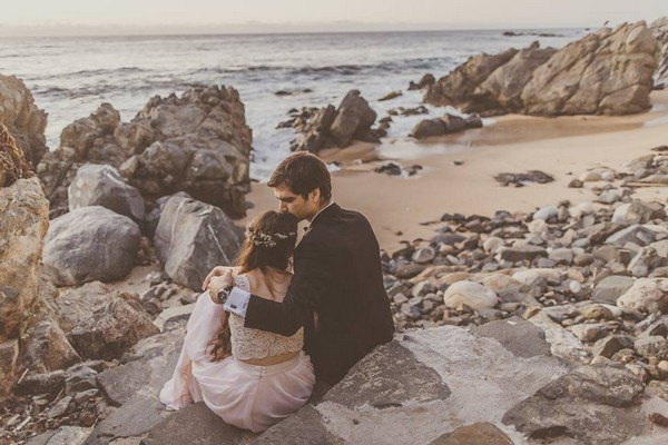 Groom kissing bride's head as they sit on rocks by the sea - Picture by Michelle Lindsell Photography