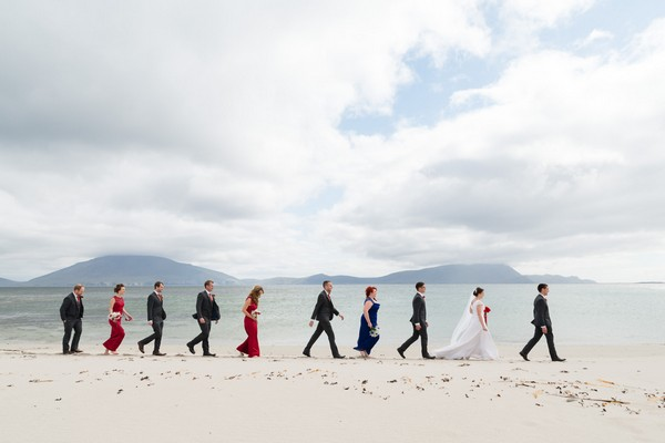 Wedding party walking in a line across beach - Picture by Andy Sidders Photography