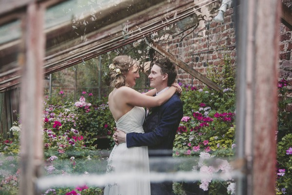 Picture of bride and groom with arms around each other taken through a window - Picture by Ella Parkinson Photography