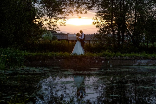 Bride and groom standing by pond in evening - Picture by Nicola Gough Photography