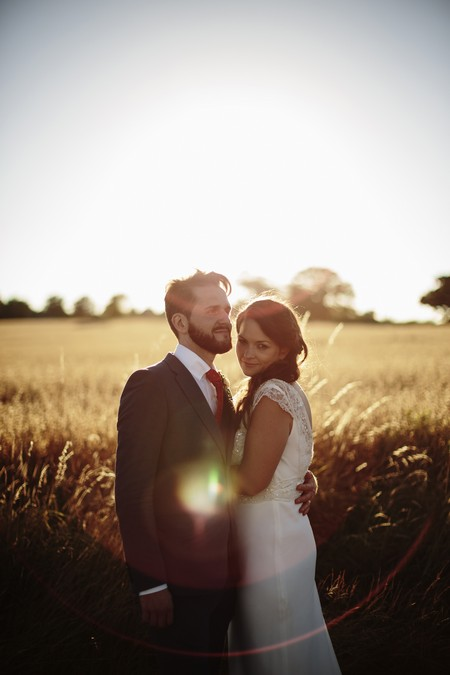 Bride and groom standing in front of wheat field in sunshine - Picture by Paul Fuller Photography