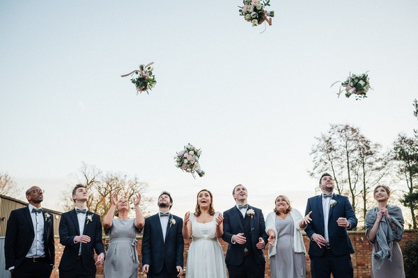 Bridal party standing in line as bride and bridesmaids throw bouquets in the air - Picture by Andrew Craner Photography