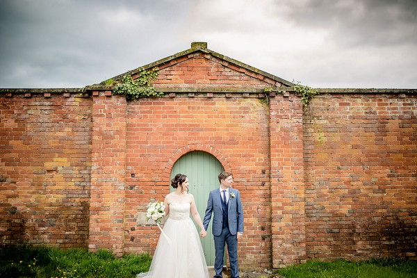 Bride and groom standing in Sugnall Walled Garden