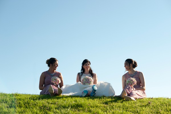 Bride and bridesmaids sitting on grass - Picture by Marina Hannah Photography