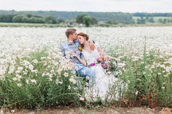 Bride and groom sitting in a field of daisies - Picture by Jo Bradbury Photography