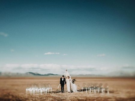 Bride and groom looking down at ground in California Salt Flats - Picture by India Earl Photography