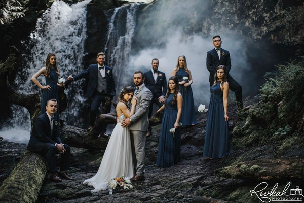 Bridal party standing on rocks in front of waterfall - Picture by Rivkah Photography