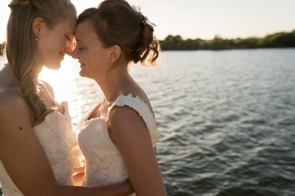 Two brides touching heads in front of water - Picture by Becky Harley Photography