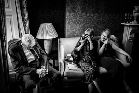 Woman taking picture of man who has fallen asleep in his chair at a wedding - Picture by How Photography