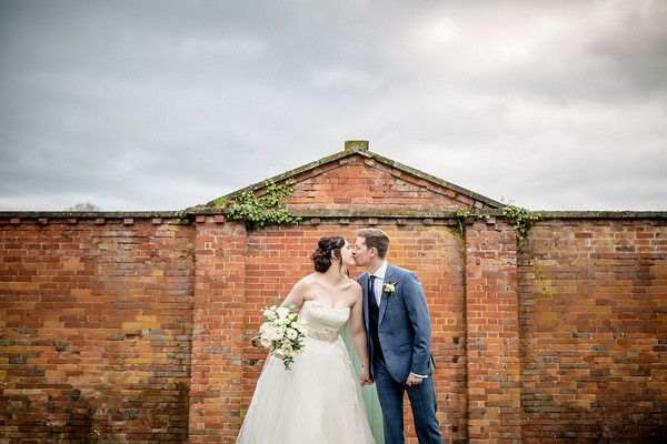 Bride and groom kissing in Sugnall Walled Garden