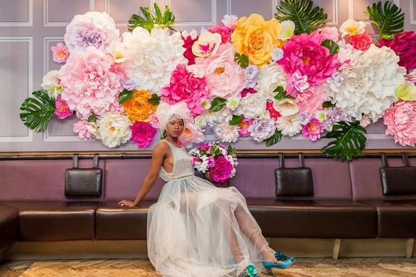 Bride sitting in front of bright and colourful flower wall