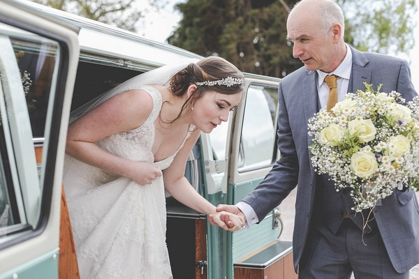 Father helping bride get out of wedding camper van