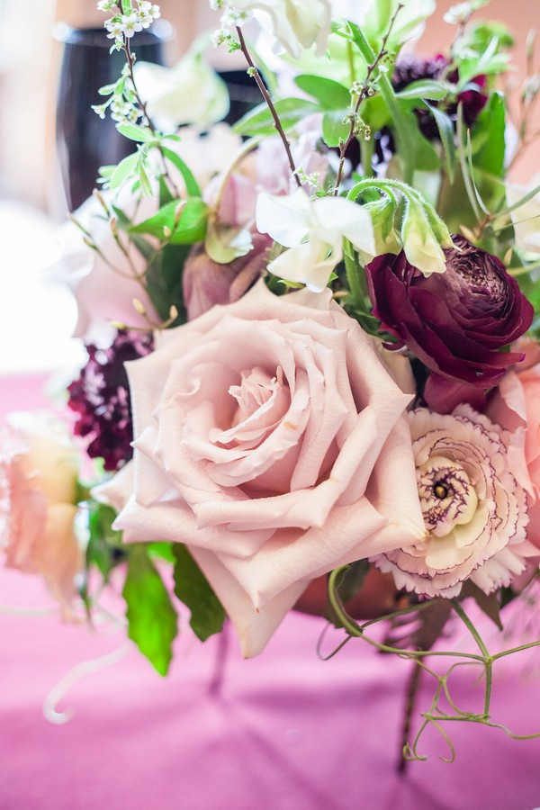 Close up of pink and purple wedding table flowers