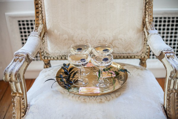 Glasses of champagne with blackberries on chair