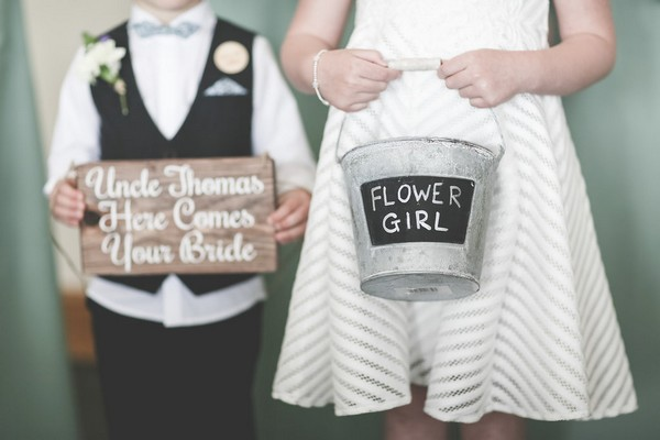 Pageboy holding sign and flower girl holding bucket