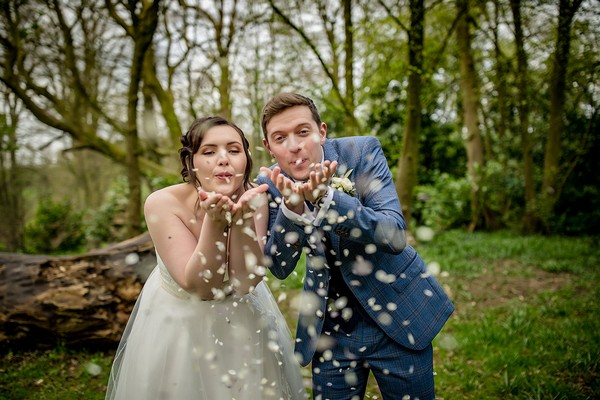 Bride and groom blowing confetti from their hands