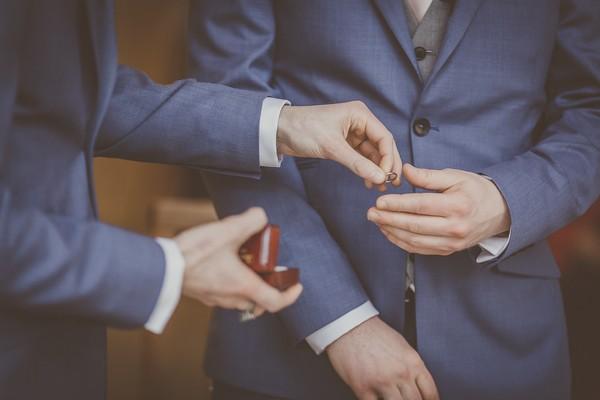 Best man handing groom wedding rings