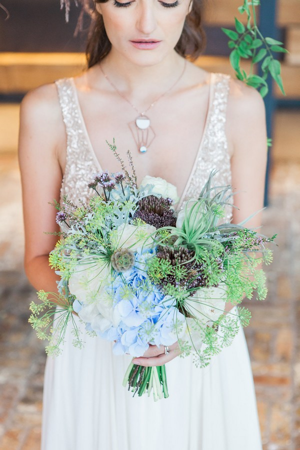 Bride holding wedding bouquet with lots of foliage