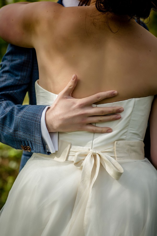 Groom's hand on bride's back