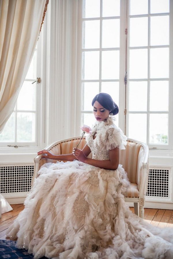 Bride sitting wearing wedding dress with ruffle detail