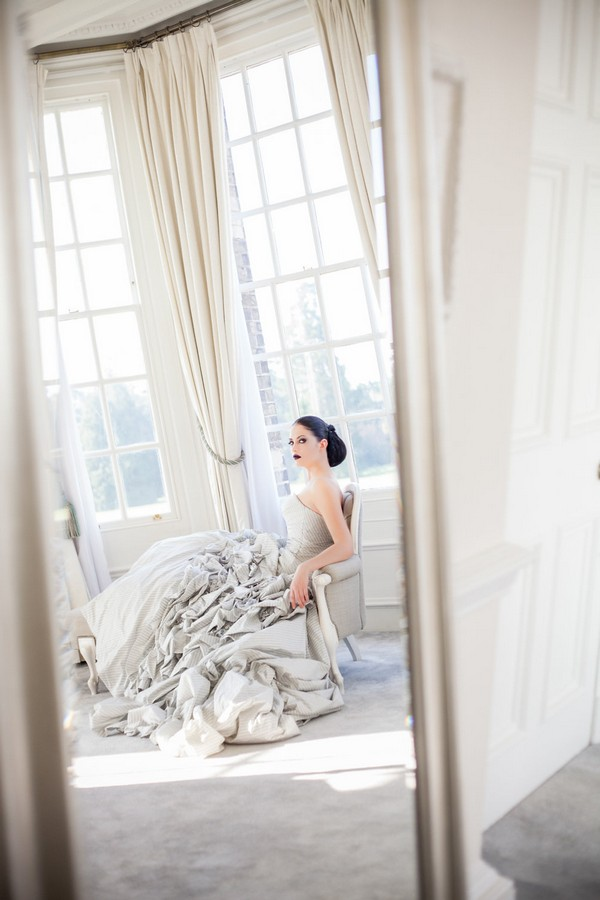 Bride sitting in chair by window at Hedsor House