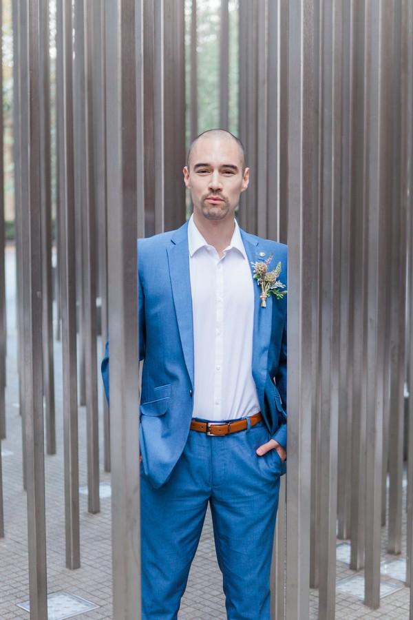 Groom in blue suit standing between poles