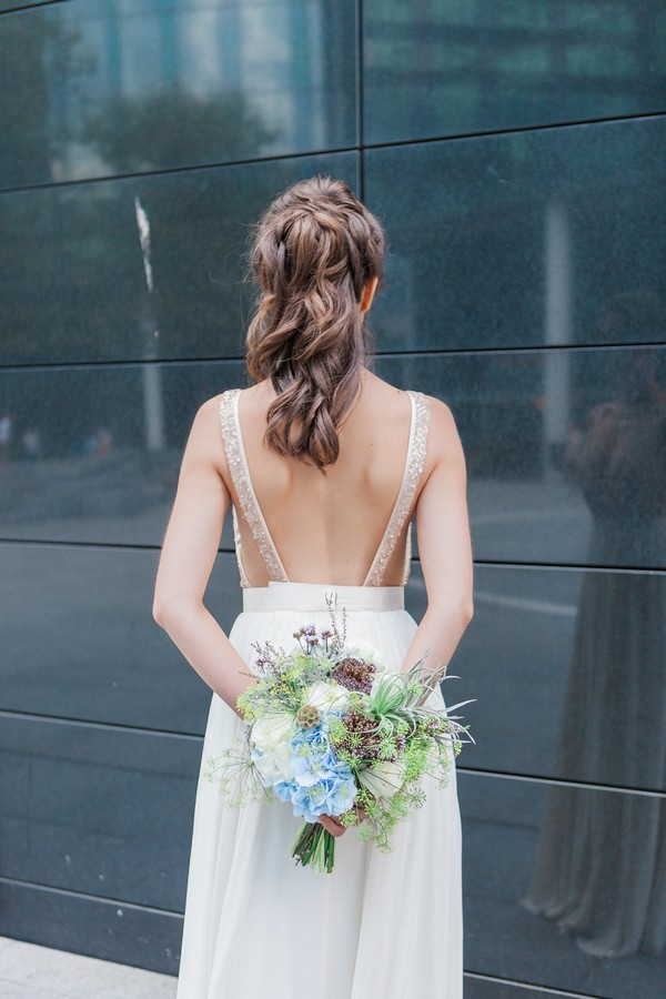Bride holding bouquet behind back