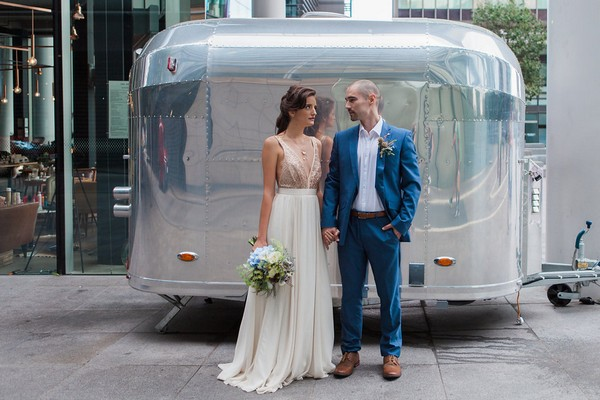 Bride and groom standing in front of metal trailer