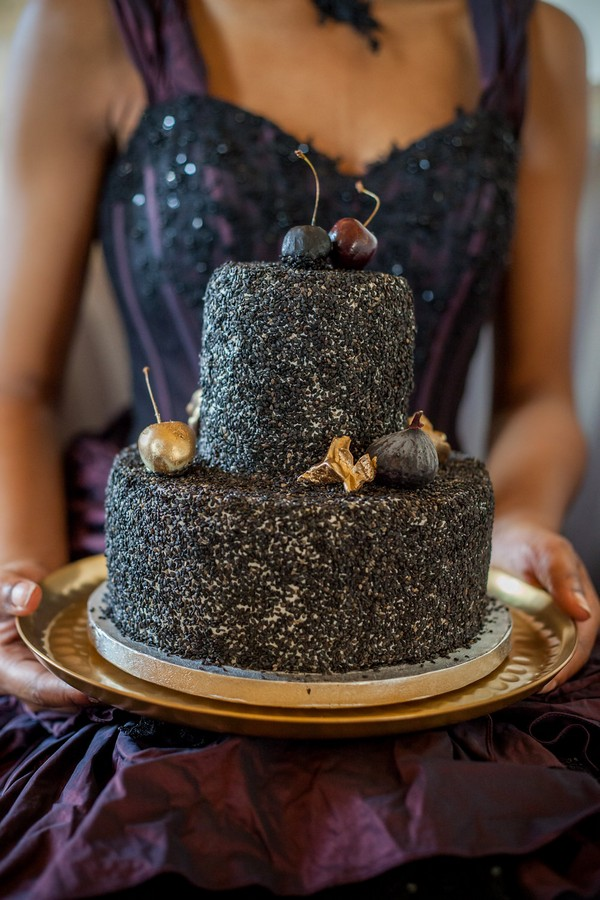 Bride holding black wedding cake