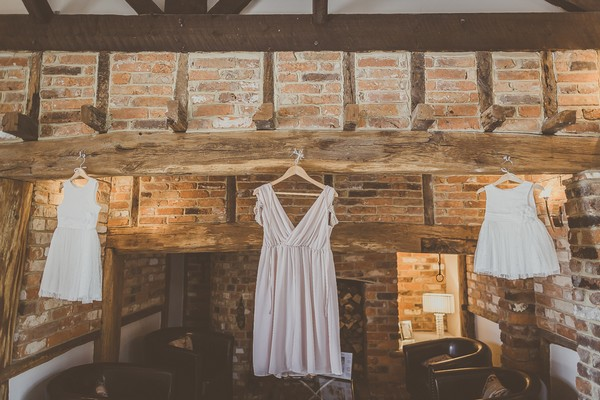 Bridesmaid and flower girl dresses hanging from beam
