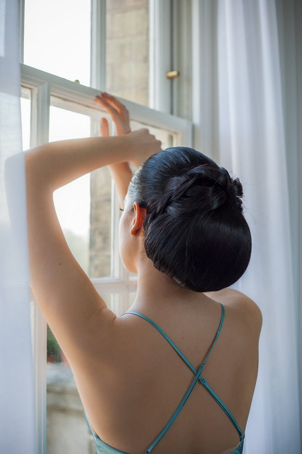 Bride with chignon hairstyle looking out of the window