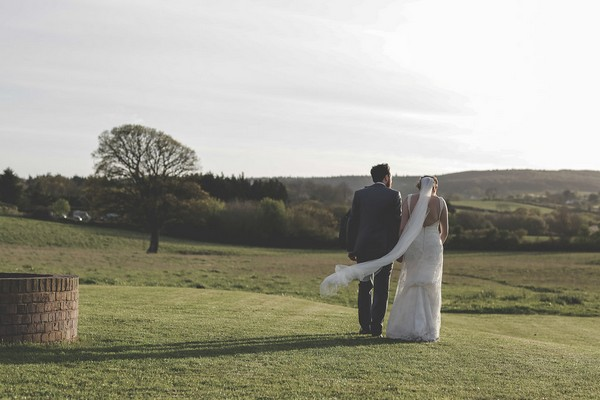 Bride and groom walking in fields at Quantock Lakes