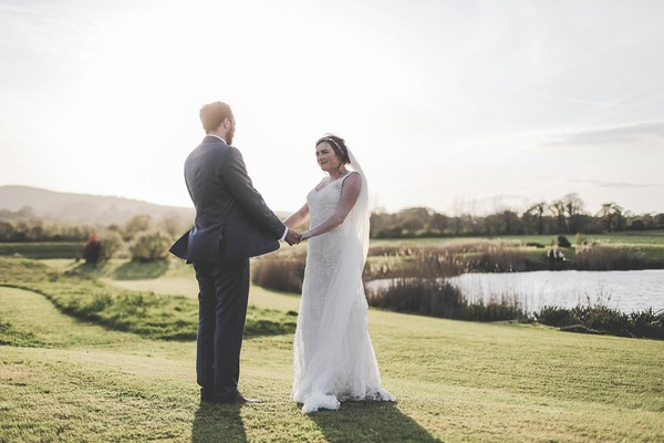 Bride and groom facing each other holding hands
