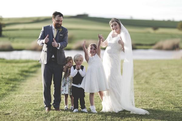 Bride, groom and children doing thumbs up