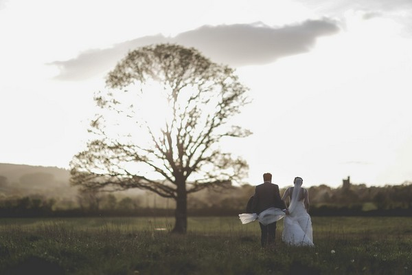 Bride and groom walking towards tree