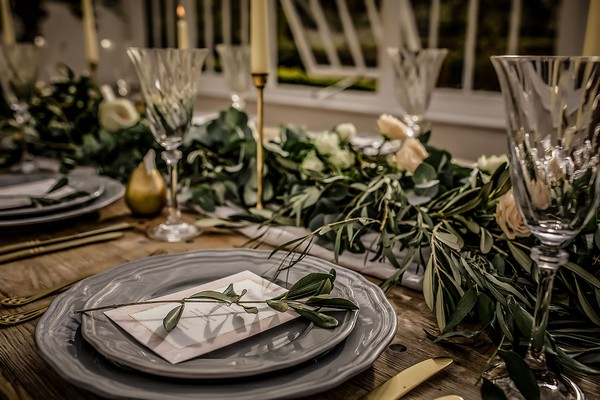 Grey plate and foliage at wedding place setting