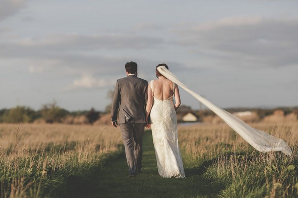 Bride and groom walking across field at Quantock Lakes