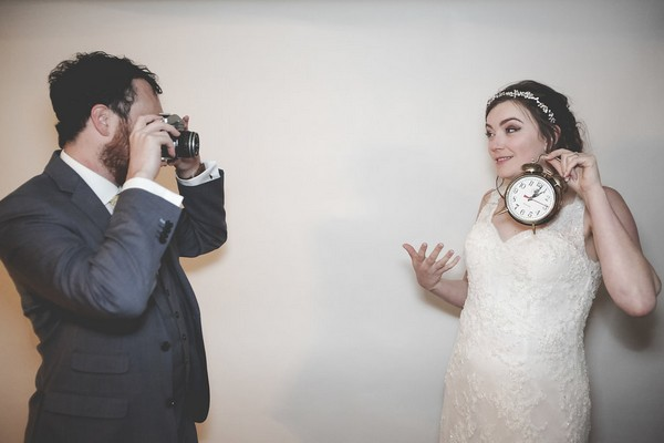 Groom taking picture of bride holding clock