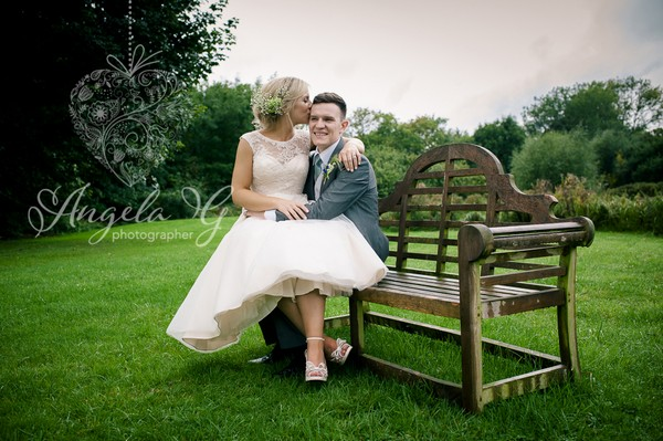 Bride sitting on groom's lap on bench - Picture by Angela G Photographer