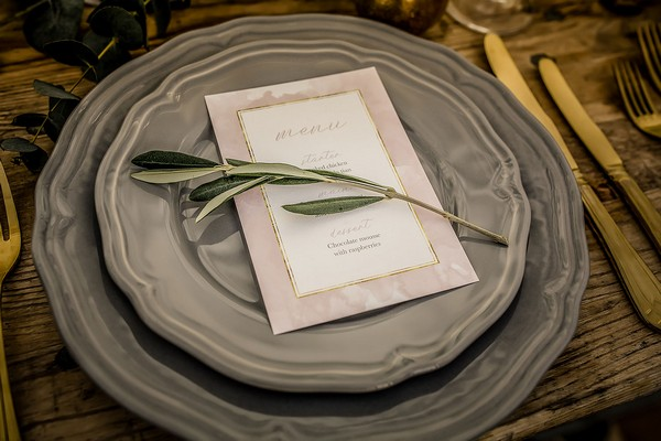 Grey plates and sage sprig at wedding place setting