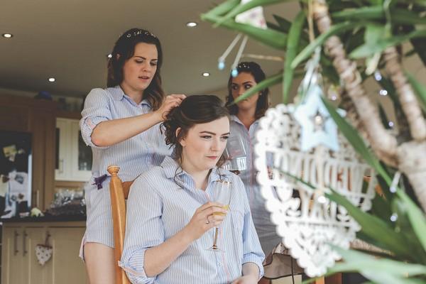Bride looking in mirror as bridesmaid helps with her hair