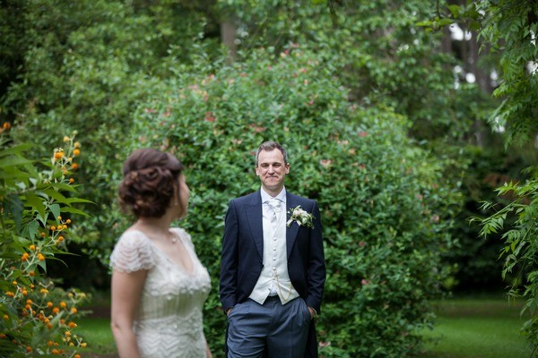Bride looking over her shoulder at groom wearing white waistcoat and cravat